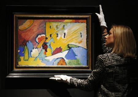 A Christie's employee poses with Wassily Kandinsky ''Studie zu 'Improvisation 3''' artwork at Christie's auction house in London June 7, 2013.